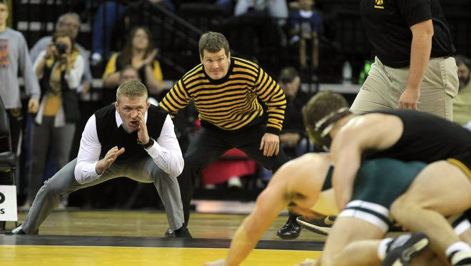 Iowa assistant Ryan Morningstar, left, and head coach Tom Brands encourage Alex Meyer during the Dec. 6 dual against Michigan State. Brands wants to see more action overall from his Hawkeyes.