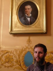 Capitol Master Decorative Painter Joshua Risner, stands beneath a portrait of Gov. Charles Croswell he painted in the style of the era. There were 12 Michigan Governors with no portraits hanging in the Capitol. Risner has begun painting them. Friday, July 13, 2018.