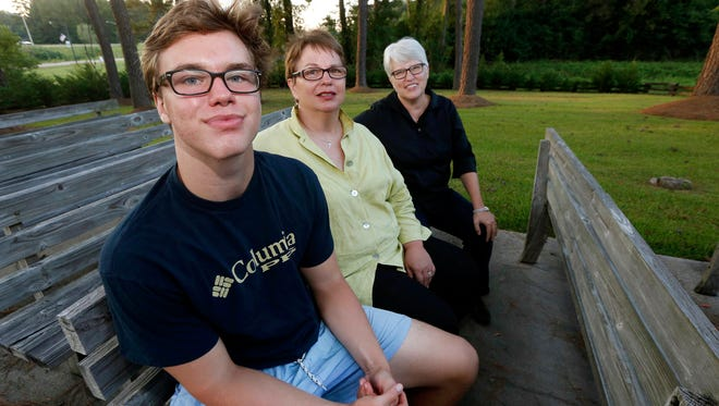 Hudson Garner, 15, sits with his mothers Kathryn Garner, center, and Susan Hrostowski in Collins, Miss., in this 2015 photo. Garner is Hudson's birth mother.