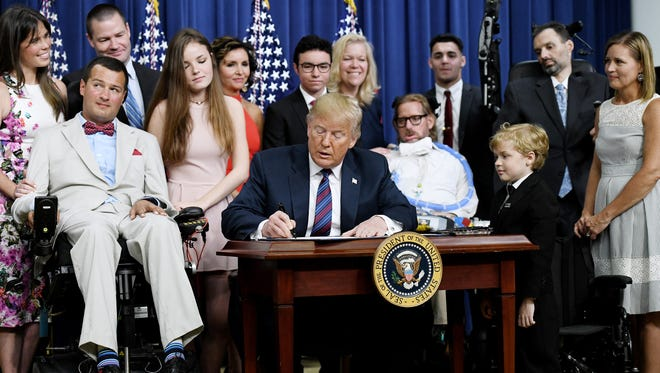 """Pewaukee residents Tim Wendler (fifth from left) and Tealyn Wendler (sixth from left) joined President Trump as he signed the """"right-to-try"""" legislation into law on May 30. The new law is intended to expand access by terminal patients to investigational drugs. Trickett Weldler died of ALS in 2015."""