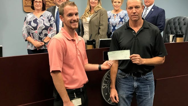 St. Lucie County Commissioners look on as Tom Rhodes, front right, co-owner of Sunshine Laundries, presents a $2,000 check to Adam Jones, Aquatics & Safety Coordinator for St. Lucie County Parks, Recreation & Facilities, during a recent County Commission meeting to fund swimming scholarships this summer.