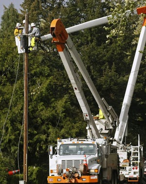 Crews from Portland General Electric work on repairing power lines.
