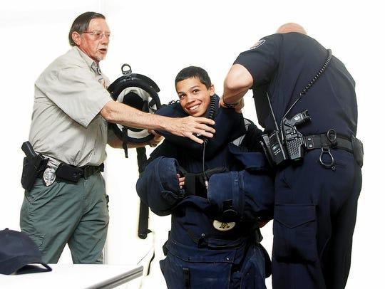 Bain Adair ties on a bomb suit with the help of Farmington