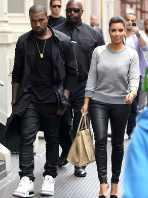 An annoyed-looking West walks with Kardashian in New York City in April 2012.