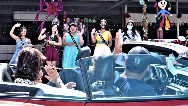 "The 2020 Fiesta Queen and court wave to passersby during Sunday's ""reverse parade"" at the Colorado State Fair."