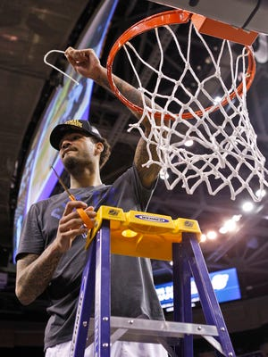 Kentucky's Willie Cauley-Stein shows of a piece of net after the Wildcats defeated Notre Dame in the Elite Eight game Saturday at Quicken Loans Arena in Cleveland.  The Wildcats go on to the Final Four in Indianapolis.  March 28, 2015. By Matt Stone, The C-J
