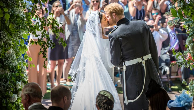 Prince Harry, Duke of Sussex kisses his wife Meghan, Duchess of Sussex as they leave from the West Door of St George's Chapel.