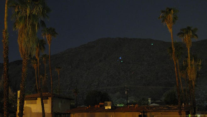 Holiday lights are once again visible on the hills above Palm Springs. No one knows who's responsible.