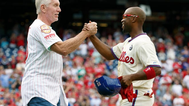 Philadelphia Phillies' Jimmy Rollins, right, celebrates his single with former Phillies' Mike Schmidt, left, during the fifth inning of a baseball game against the Chicago Cubs, Saturday, June 14, 2014, in Philadelphia. This single gives Jimmy Rollins the all time hits mark for the Philadelphia Phillies over Mike Schmidt. (AP Photo/Chris Szagola)