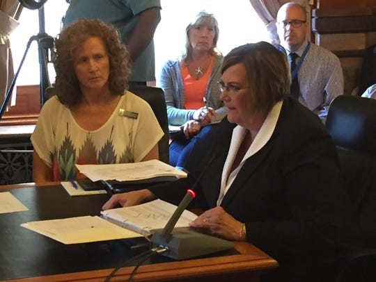 Mikki Stier, the state's Medicaid director, right,