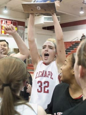 Lenape's Maddie Sims hoists the trophy after Lenape beat Cherokee 37-29 in the South Jersey Group 4 girls' basketball final on Tuesday.