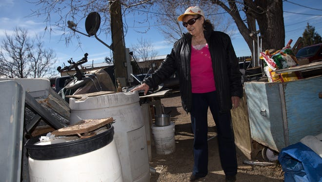 AV Water Co. customer Irene Gallegos talks Friday about the water barrels she used to store water in at her property in Crouch Mesa after her water service was cut off for nonpayment.
