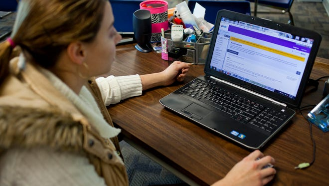 In an 2015 photo, Blue Water Virtual School math teacher Megan Thompson looks over the dashboard she uses to communicate with her students at Croswell-Lexington High School. Authorities say she died in a car crash Friday morning.