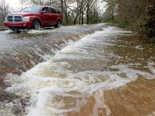 A vehicle drives along a flooded section of Hayneville