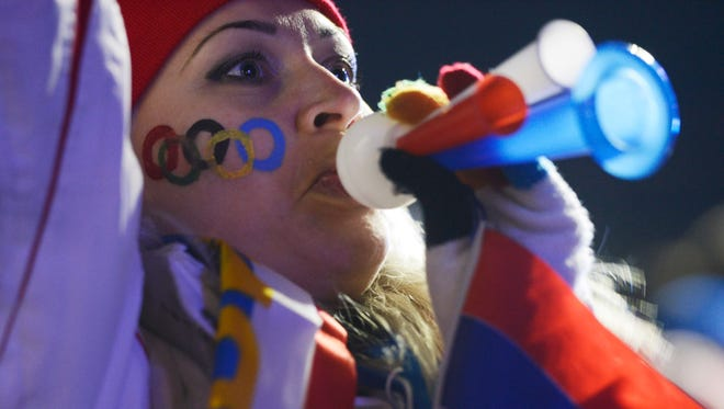 A woman celebrates as she watches a big screen broadcast of the opening ceremonies at the Sochi City Live site during the Sochi 2014 Olympic Winter Games.