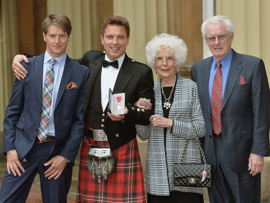 LONDON, ENGLAND - OCTOBER 14: John Barrowman (2nd L) poses with husband Scott Gill (L) and parents Marion and John Barrowman after being awarded an MBE at an investiture ceremony at Buckingham Palace on October 14, 2014 in London, England.