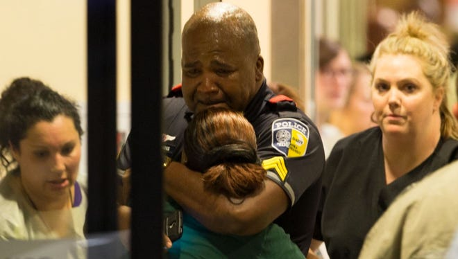 A Dallas Area Rapid Transit police officer receives comfort at the Baylor University Hospital emergency room entrance July 7, 2016, in Dallas. Police say one rapid-transit officer has been killed and three injured when gunfire erupted during a protest in downtown Dallas over recent fatal shootings by police in Louisiana and Minnesota.