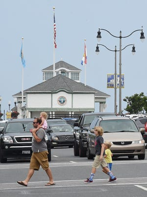 Cars wait at a red light on Rehoboth Avenue as pedestrians cross the street during the July 4 holiday weekend.