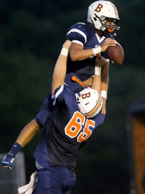 Blackman's Camron Curtis (65) hoists teammate Taeler Dowdy (3) in the air after Dowdy scored a touchdown in the game against Riverdale at Blackman, on Friday Sept. 4, 2015.