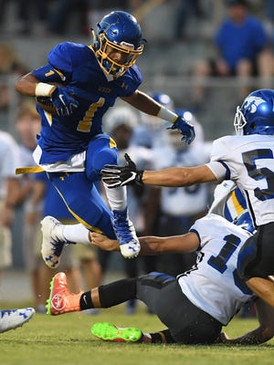 Woodmont's Preston St. Martin (13) tries to bring down Wren's Tyrell Jackson (1) on Friday in Piedmont.