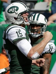 FILE - In this Sept. 24, 2017, file photo, New York Jets quarterback Josh McCown (15) celebrates with teammate Robby Anderson (11) after they connected for a touchdown during the first half of an NFL football game against the Miami Dolphins in East Rutherford, N.J. McCown was signed by the Cleveland Browns two years ago to bring stability and leadership to a constantly revolving quarterback carousel. Sound familiar? McCown is being asked to do the same with the Jets, and so far he's got two wins to show for it.  (AP Photo/Seth Wenig, File)