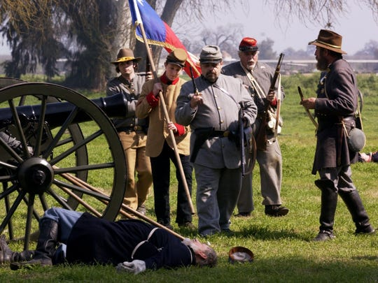 During a re-enactment of a skirmish between The Union of the Tennessee and the Confederate Army of Tennessee, Confederates Bert Ramos, of Fresno, left, John Henry, of Visalia, Chris Bowman, of Fresno, Wayne Truex, of Fresno, and Charles Henry, of Visalia, at right, check on Union casualties including Harry Webb, of Lodi.