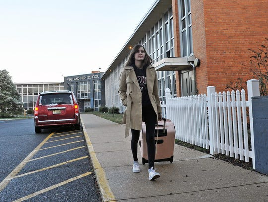 Vineland High School junior Juliet Brown wheels a suitcase