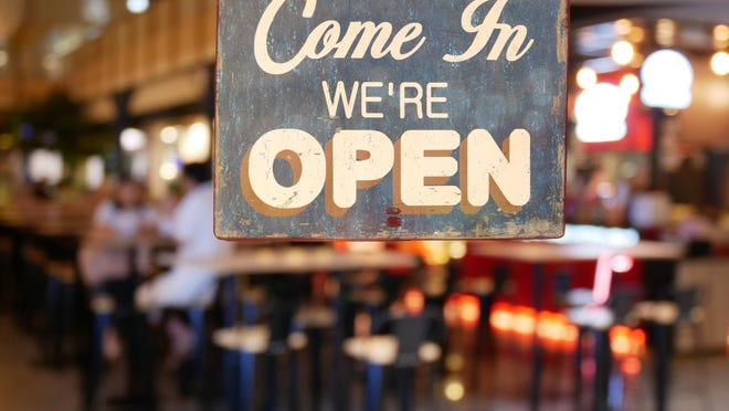 A sign on a restaurant's glass door reads Come in, we're open.