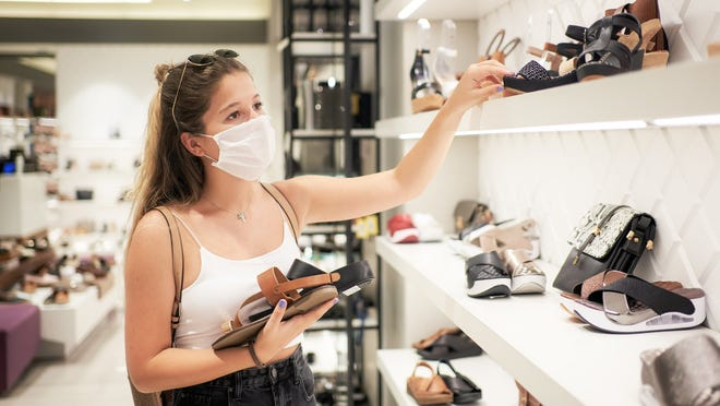 A masked woman shops for shoes in a retail footwear store.