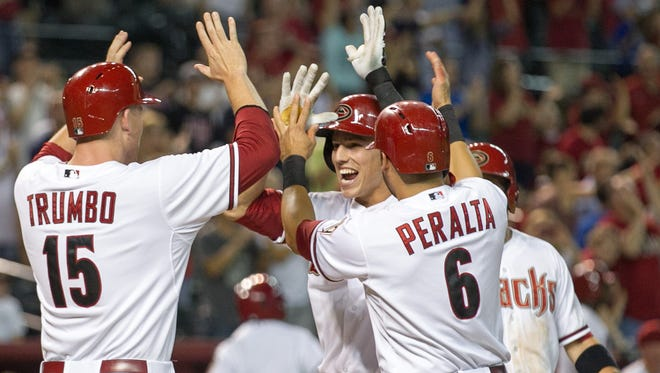 Arizona Diamondbacks infielder Jake Lamb celebrates with teammates at home plate after hitting a grand slam against the Colorado Rockies in the sixth inning at Chase Field in Phoenix on Friday, August 29, 2014.
