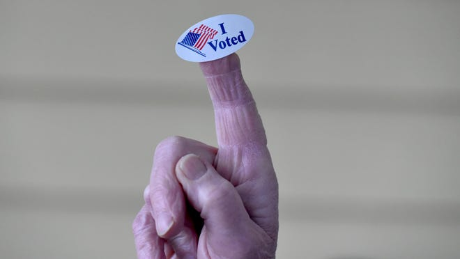 A voter shows off their sticker at the Hyannis Youth & Community Center during the state presidential primary in March. Early in-person voting for the Nov. 3 election starts on Saturday.