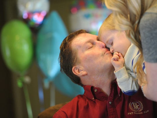 Paul Miller gives his grandson Wilder a kiss during his welcome home party in his Spring Garden home on Tuesday, April 16, 2013. Miller was struck with Streptococcus Pneumoniae on Sunday, Feb 3, 2013, resulting in the amputation of his hands and feet. Jason Plotkin - Daily Record/Sunday News