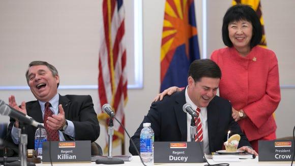 Arizona Governor Doug Ducey (center) looks at a birthday