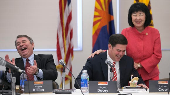 Arizona Governor Doug Ducey (center) looks at a birthday cupcake as Senior Associate Christine Wilkinson (right) and Mark Killian, (left) chair of the Arizona Board of Regents, look on, during an Arizona Board of Regents meeting on the ASU campus in Tempe on Thursday, April 9, 2015. Wilkinson brought Ducey a cupcake for his birthday during the meeting.
