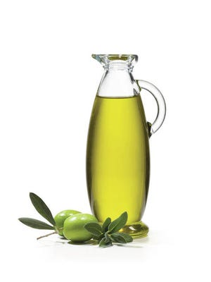 A bottle of olive oil with two olives and sage. Photo by Dreamstime/TNS