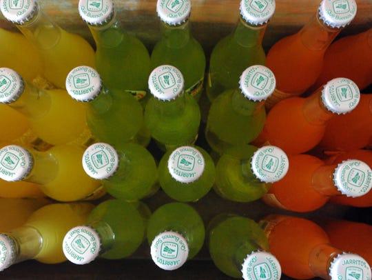 Bottles of Jarritos soft drinks sit in a planter inside