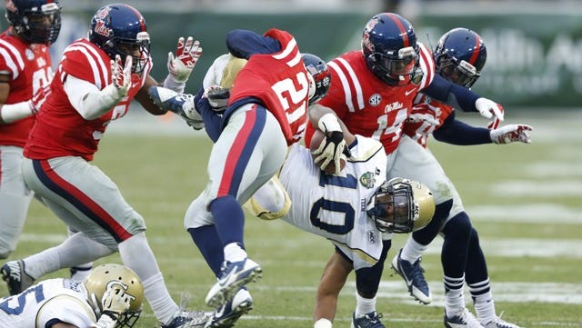 NASHVILLE, TN - DECEMBER 30: Synjyn Days #10 of the Georgia Tech Yellow Jackets gets tackled for a loss of yardage by Senquez Golson #21 of the Ole Miss Rebels in the first half during the Franklin American Mortgage Music City Bowl at LP Field on December 30, 2013 in Nashville, Tennessee. (Photo by Joe Robbins/Getty Images)
