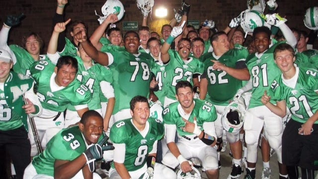 Novi players celebrate after their upset 50-33 football win over previously unbeaten South Lyon.