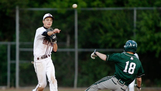 Okemos' Tommy Deppong, left, throws to first to try to turn a double play against Portland St. Patrick's Cooper Diamond (18) Monday, May 22, 2017, at Municipal Park Lansing, Mich. Diamond was out but the runner was safe at first. Okemos won 4-0.