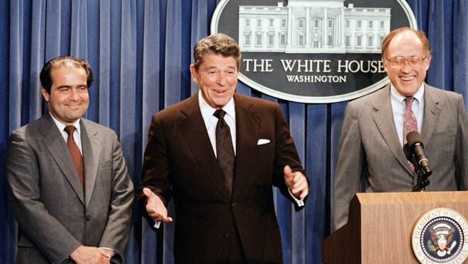 In this June 17, 1986, file photo, President Ronald Reagan speaks at a news briefing at the White House in Washington, where he announced the nomination of Antonin Scalia, left, to the Supreme Court as a result of Chief Justice Warren E. Burger's resignation. William Rehnquist is at right.