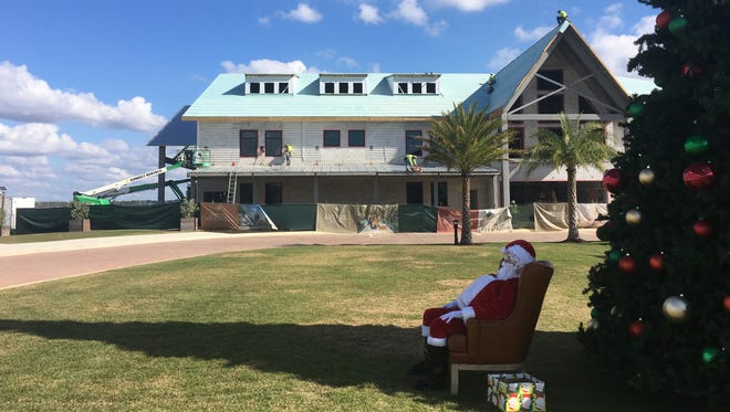 Santa Claus, depicted by town ambassador Rick Vorell, sits in the shade of a Christmas tree on a warm December day as he awaits a visit from schoolchildren. In the background, construction work is being done on the wellness center.