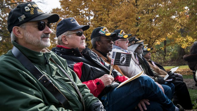 Attendees hold flags during the Veterans Day program hosted by Vietnam Veterans of America Chapter 10 Saturday, Nov. 11, 2017, at the Vietnam Memorial in Eden Park.