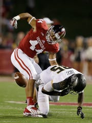 Indiana's Marcus Oliver (44) strips the football from Missouri's Marcus Lucas (85) during the first half of an NCAA college football game Saturday, Sept. 21, 2013, in Bloomington, Ind.  (AP Photo/Darron Cummings)