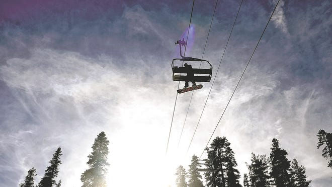 A snowboarder rides on the Comstock Lift at Northstar California.