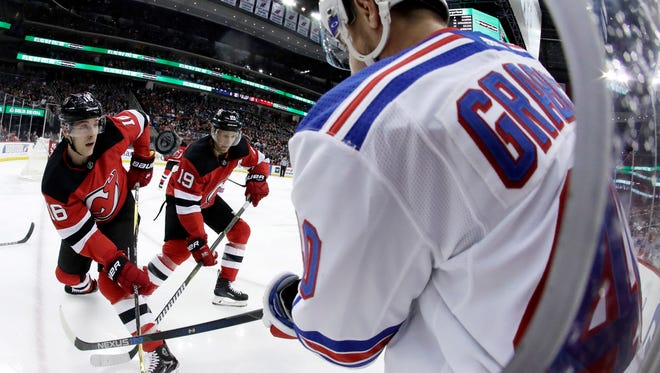 The puck kicks up as New York Rangers right wing Michael Grabner, right, of Austria, competes for the puck with New Jersey Devils defenseman Steven Santini (16) and center Travis Zajac (19) during the first period of an NHL hockey game Thursday, Dec. 21, 2017, in Newark, N.J. (AP Photo/Julio Cortez)