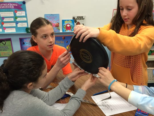 Left to right Central School 5th graders Samantha Traister, Lauren Rich, and Claire Gillenwater measure the circumference and diameter of a Frisbee to celebrate Pi Day on March  14.