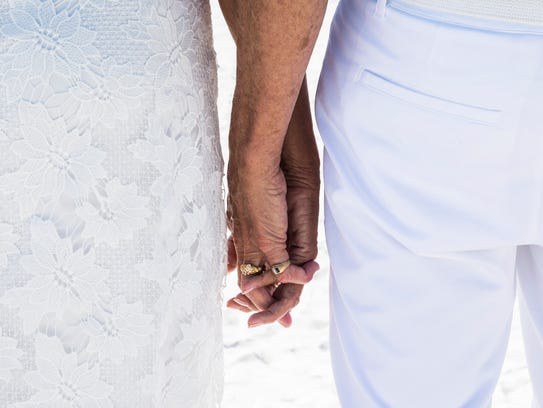 A couple holds hands as their renew their vows during