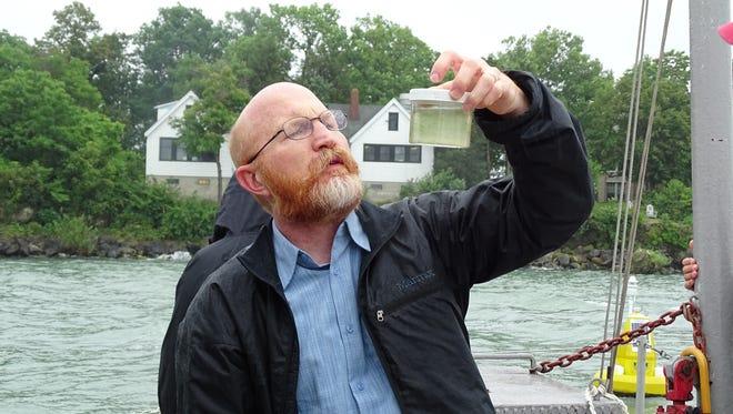 Tom Bridgeman, harmful algal bloom researcher at the University of Toledo, examines a water sample taken from Lake Erie near Gibraltar Island in 2015.