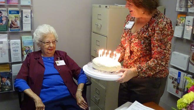 Myrtle Koch, who volunteers twice a week at the Golden Threads office at ProMedica Memorial Hospital, receives a red velvet birthday cake baked by Golden Threads director Annette Overmyer on Monday, the day before Koch's 98th birthday.