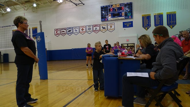 Kara Butler reads a letter for her mother Tammy Jeffers, who was honored as a breast cancer survivor at the West Muskingum-Crooksville High School volleyball game on Thursday night. The schools raised more than $1,600 to help Jeffers pay for medical costs.